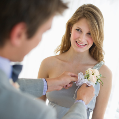 A guy pinning a corsage on his date for the dance. Credit: Tetra Images on gettyimages.com
