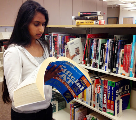 ABOVE: Sophomore Anvita Valluru tries to balance studying for her SAT exam with helping organize books at the library.