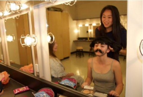 Lilla Lavanakul helps her double cast, Keiva Bradley into her Count Gregor wig as she gets ready for rehearsal.