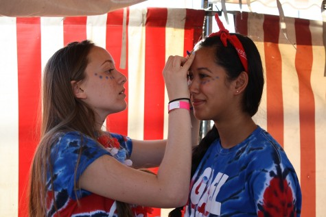 Dublin High senior, Neena Dye (left) helps apply face paint to senior, Britney Lorenzana (right) in preparation for the football game. Majority of the crowd seen at the carnival and game were head-to-toe decked out in red, white, and blue supporting their home team.
