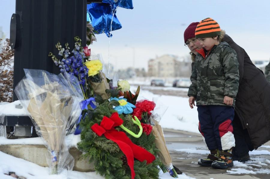 COLORADO SPRINGS, CO - NOVEMBER 29: Nasya Fair looks at the growing memorial for the shooting victims with her son Korbyn, 4, at Fillmore Street and Centennial Boulevard on November 29, 2015 in Colorado Springs, Colorado. The investigation moves into its third day after a gunman attacked a Planned Parenthood, killing three and injuring nine. (Photo by Brent Lewis/The Denver Post via Getty Images)