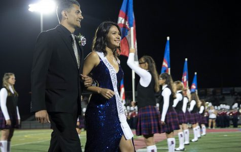 2017 Homecoming Queen Belle Enriquez walks down the football field with her father.