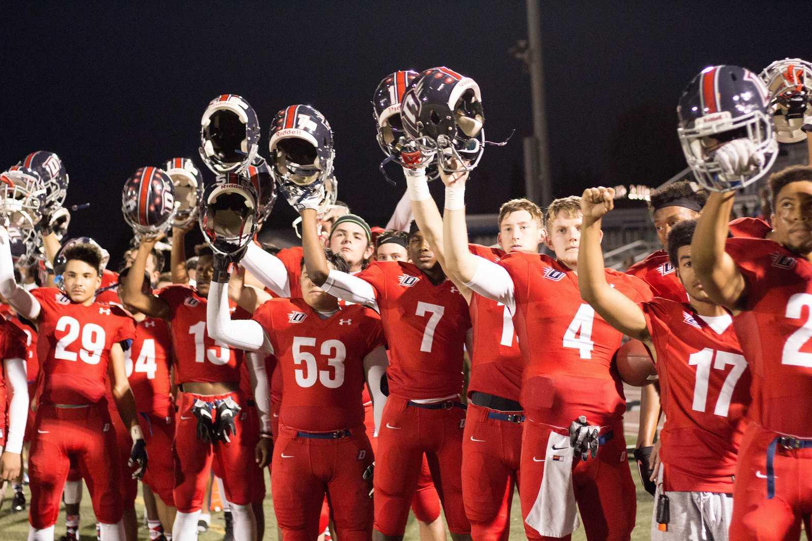 Ryan Hair DHS football players raise their helmets during the National Anthem.