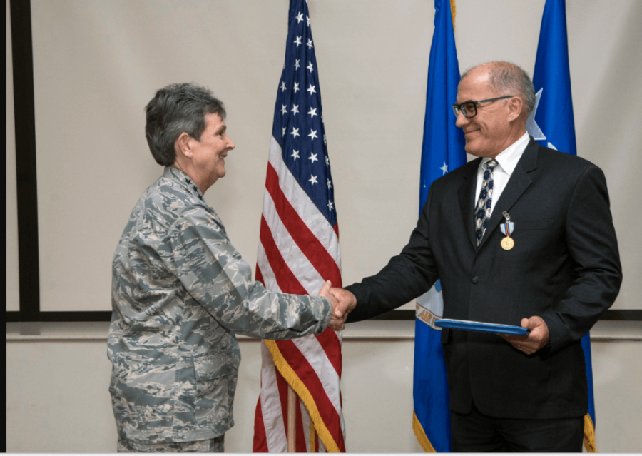 Gen. Ellen Pawlikowski congratulates Greg Gangnuss after presenting him with the Air Force Civilian Award for Valor during a Feb. 22 commander's call at Joint Base San Antonio, Texas.