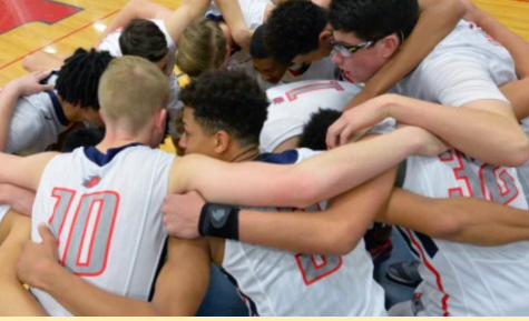 The men's varsity basketball team in a group huddle.