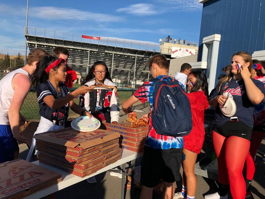 Leadership students serve pizza at the tailgate.