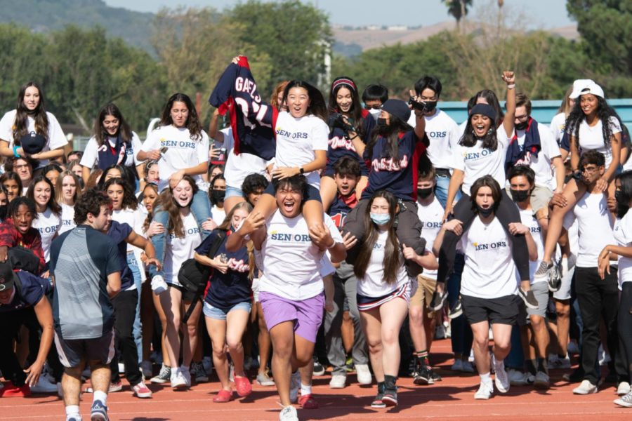 Seniors, clad in class shirts, stampeding across the track. (Photo courtesy of Dublin High School)