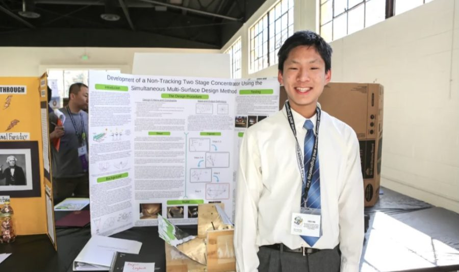 Student competitor displaying his design project at the fair
